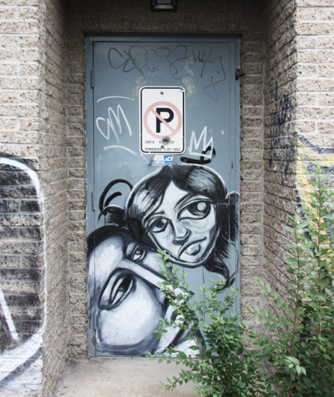 Labrona (bottom) and artist who asked to remain anonymous (top) on door in alley behind St-Denis