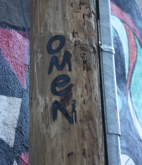 Omen tag in front of one of his murals
