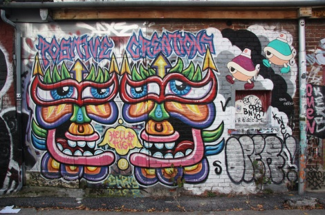 A positive creation by Chris Dyer and two wheatpastes by Turtle Caps (top right) in alley between St-Laurent and Clark