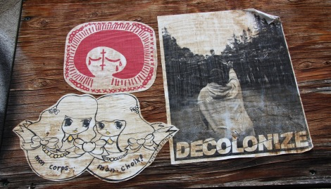 paste-ups by Stela (bottom left) and Swarm for Decolonizing Street Art (top left and right)