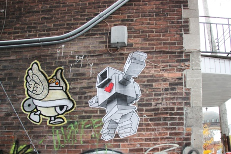 Lovebot (right) and Turtle Caps (left) wheatpastes in alley behind St-Laurent on the corner of St-Viateur