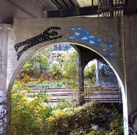 Swarm piece painted high under an overpass