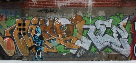 Nixon graffiti and OXLXO stencil behind building on de Gaspé