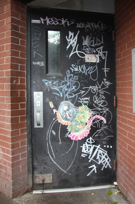 Door in alley between St-Laurent and Clark featuring mainly a wheatpaste by Lily Luciole, stickers by TikTok, Cif and Meat and lots of tagging including Tik Tok in bottom right corner