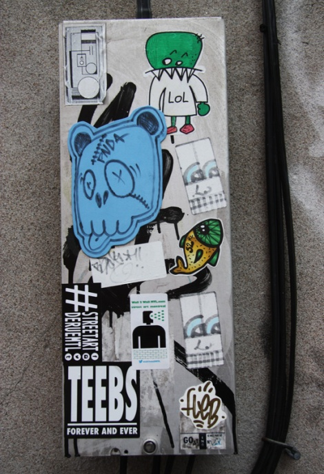 Stickers by Tik Tok (top left), National Zombi (top right), 52Hz (fish) and Fleb (bottom right), plus pasted card by Pnda (blue). In alley between St-Laurent and Clark