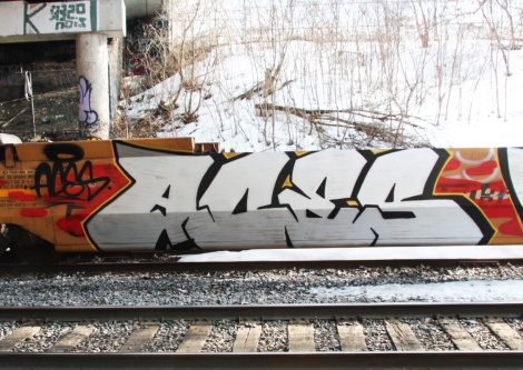 Graffiti by Aces on parked train.