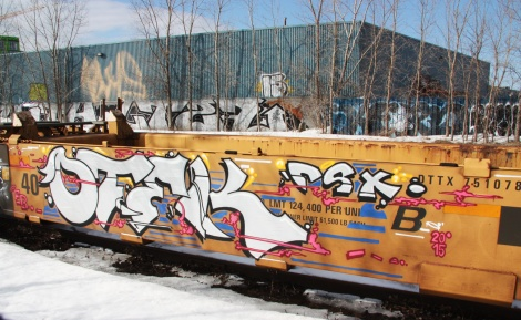 Graffiti by Otek-CSX on parked train.