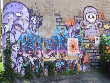 Scaner graffiti within Astro mural. Visible in the middle is a wheatpaste by Graffiti Knight.
