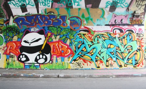 Reabs (left, twice) and Secs (right) at the Rouen legal graffiti tunnel; peeping cat above is by Mr Chose