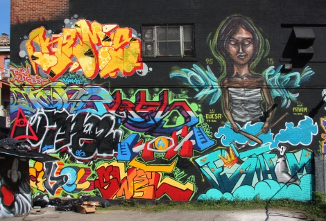 Wall produced during the 2015 edition of the Under Pressure Festival featuring Kems (top left), Elicser Elliott (character), Fathom (bottom right) and many others