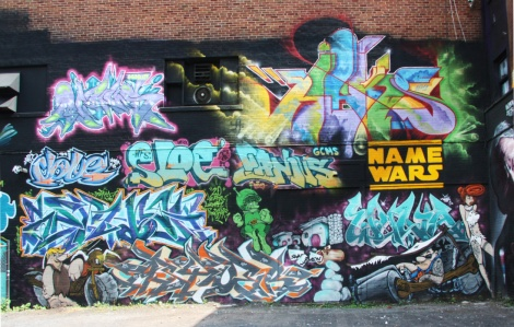 Wall produced during the 2015 edition of the Under Pressure Festival featuring Minus (top left), Haks (top right), Dove (middle left), Sloe (left of middle), Ganjus (right of middle), Serna (ground left letters), Strike (characters), Asyne (ground middle letters) and Wuna (bottom)
