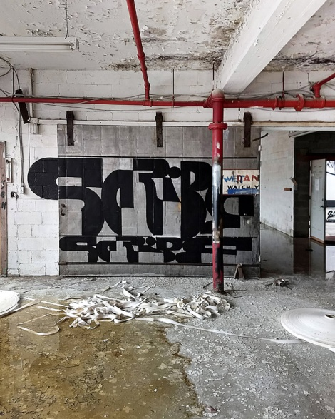 interactive graff piece on sliding door by Scribe in an abandoned building