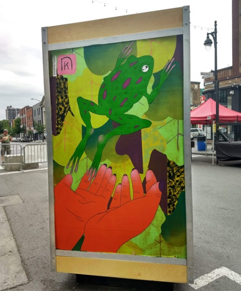 Nikki Kuentzle on the reverse of an ad/info board for the 2018 edition of Mural Festival