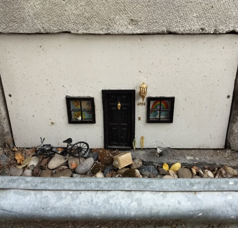 Miniature installation replicating a Plateau housefront with bicycle, cat, etc.